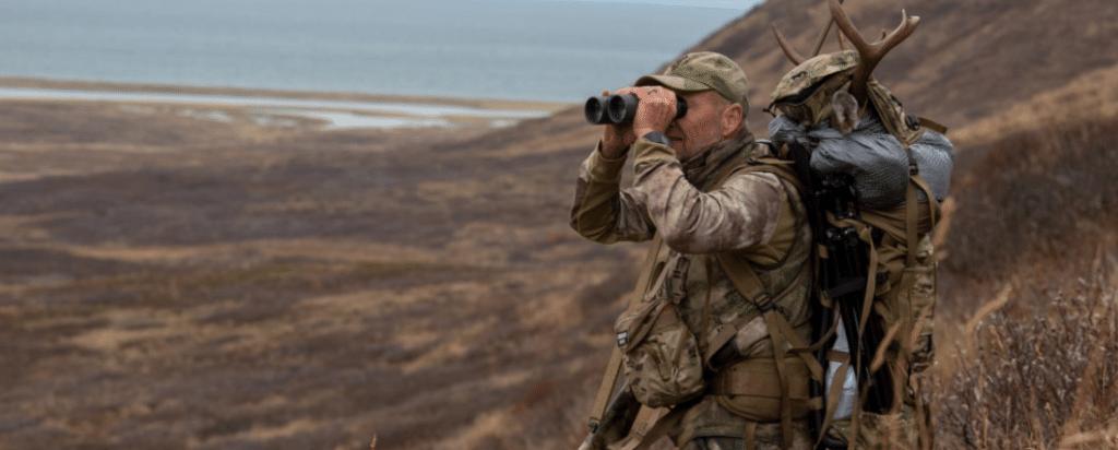 deer hunter using binoculars