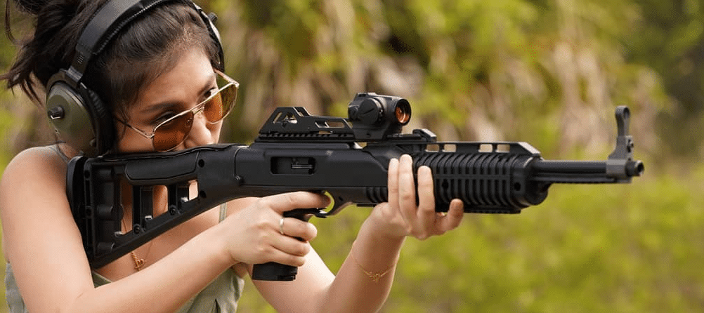 a girl shooting hi point pcc with sig red dot